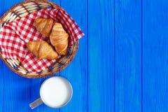 杯子牛奶用在桌上的新月形面包 免版税库存图片