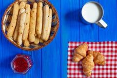 杯子牛奶用新月形面包、grissini和自创山莓果酱 免版税库存照片