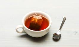 杯子用热水填装了并且浸洗了袋子红茶 杯子用开水、茶袋和匙子填装了在白色 免版税库存图片