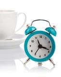 从杯子的蓝色闹钟在白色的茶碟 库存照片