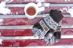 杯子茶和妇女` s在冬天编织了在一条长凳,下面雪的手套 顶视图 库存图片