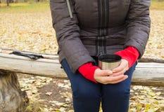 杯子茶,在手妇女的咖啡在秋天公园 库存图片