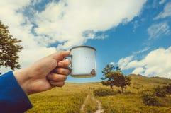 杯子水或热的茶在手中在绿草山的一个偏僻的旅游远足概念与土路 库存照片