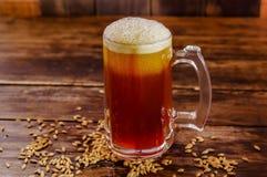 杯室内看法啤酒用在基地的麦子在被弄脏的背景的一张木桌上 免版税库存照片
