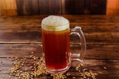 杯室内看法啤酒用在基地的麦子在被弄脏的背景的一张木桌上 免版税库存图片