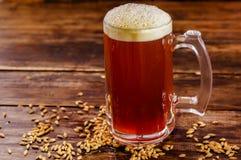 杯室内看法啤酒用在基地的麦子在被弄脏的背景的一张木桌上 库存照片