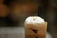 杯巧克力奶昔和坚果在木背景 免版税图库摄影