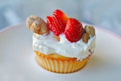 杯形蛋糕做了用鸡蛋并且冠上了用酸奶、草莓和被烘烤的狗款待在白色板材 库存图片
