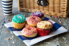 杯形蛋糕和油炸圈饼与野餐篮子 库存图片