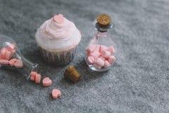 杯形蛋糕和瓶有桃红色巧克力心脏的,蛋白软糖 免版税图库摄影