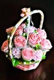 杯形蛋糕和蛋白软糖花束在藤条篮子 库存照片