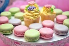 杯形蛋糕和macarons在桃红色backgound 免版税图库摄影