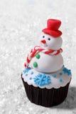 杯形蛋糕在白色雪的圣诞节雪人 免版税库存图片