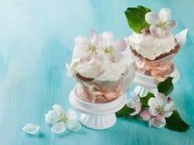 杯形蛋糕或松饼与鲜花 库存照片