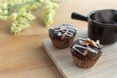 杯形蛋糕杏仁 巧克力蛋糕洒与杏仁供食用热的咖啡 可口的蛋糕 蛋糕用在木桌上的糖粉 库存照片