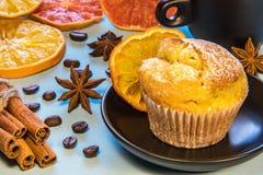 杯形蛋糕洒与在一个黑色的盘子的糖粉末在一杯咖啡旁边用桂香豆和切好的桔子 免版税库存图片
