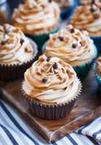 杯形蛋糕用乳脂干酪、焦糖和巧克力 库存照片