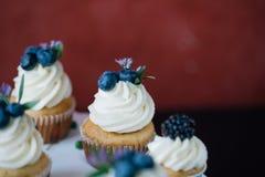 杯形蛋糕用在黑桌上的莓果 自创 宏指令 莓和蓝莓 没有染料的概念自然食物 图库摄影