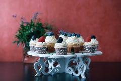 杯形蛋糕用在黑桌上的莓果 自创 拷贝空间 莓和蓝莓 没有染料的概念自然食物 库存照片