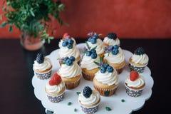杯形蛋糕用在黑桌上的莓果 自创 拷贝空间 莓和蓝莓 没有染料的概念自然食物 库存图片
