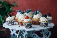 杯形蛋糕用在黑桌上的莓果 自创 拷贝空间 莓和蓝莓 没有染料的概念自然食物 免版税图库摄影
