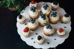 杯形蛋糕用在黑桌上的莓果 自创 拷贝空间 免版税库存图片