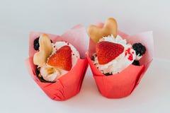 杯形蛋糕用奶油色和新鲜的草莓和黑莓莓果和心形的曲奇饼 库存图片