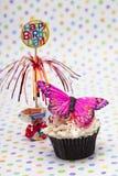 杯形蛋糕的图象与蝴蝶和生日快乐缩样的  库存照片