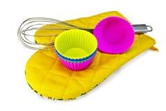 杯形蛋糕的模子与在黄色握持热锅的布垫子的搅拌器 库存照片