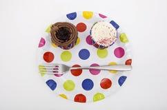 杯形蛋糕顶视图在多彩多姿的板材的在白色背景 库存照片