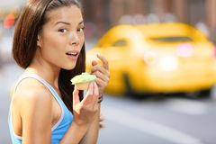 杯形蛋糕-妇女被捉住吃杯形蛋糕快餐 图库摄影