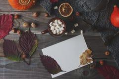 杯恶用蛋白软糖、自创秋天明信片、秋天叶子、南瓜和坚果在土气木背景 免版税库存照片