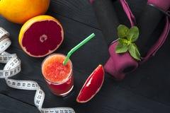 杯戒毒所葡萄柚汁、哑铃和测量的磁带 免版税图库摄影