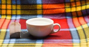 杯或白色瓷杯子有透明热水和袋子的茶 酿造在陶瓷杯子的茶的过程 被填装的杯子 免版税库存照片