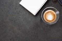 杯拿铁咖啡、笔记本和手表在黑背景 免版税库存图片