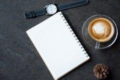杯拿铁咖啡、笔记本和手表在黑背景 免版税库存照片