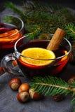 杯新年` s仔细考虑了酒用一根肉桂条和榛子在冷杉分支背景  免版税库存照片