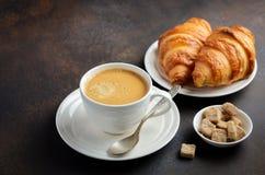 杯新鲜的咖啡用在黑暗的背景的新月形面包 免版税库存图片