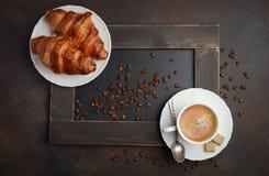 杯新鲜的咖啡用在黑暗的背景的新月形面包 库存图片