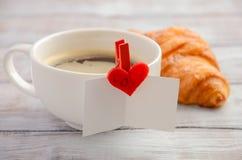 杯新鲜的早晨咖啡用新月形面包 华伦泰` s日概念 库存图片
