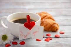 杯新鲜的早晨咖啡用新月形面包 华伦泰` s日概念 库存照片