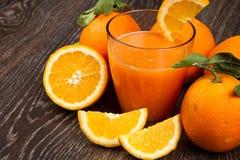 杯新鲜的橙汁和桔子在木背景 免版税库存图片