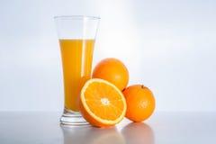 杯新鲜的橙汁和橙色果子 免版税库存照片