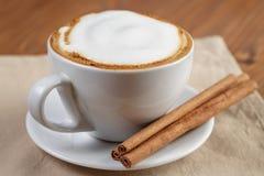 杯新鲜的热的热奶咖啡用肉桂条 免版税图库摄影