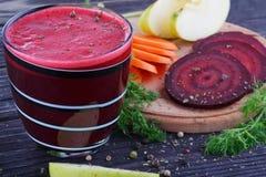 杯新鲜的甜菜根、苹果和红萝卜汁 免版税库存图片