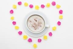 杯无奶咖啡桃红色黄色玫瑰被计划以在白色背景的心脏的形式 免版税库存图片