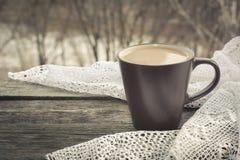 杯无奶咖啡用在窗口前面的牛奶和在木背景的一根鞋带 免版税库存照片