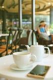 杯有一个手机的热的绿茶和白色茶壶在咖啡馆的表上 免版税库存照片