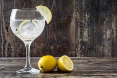 杯杜松子酒补品用在木头的柠檬 免版税库存图片