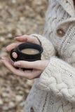 杯杯子热的饮料在女性手上在温暖的毛线衣 免版税图库摄影
